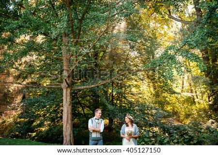 Happy girl and her boyfriend walking in park. - stock photo