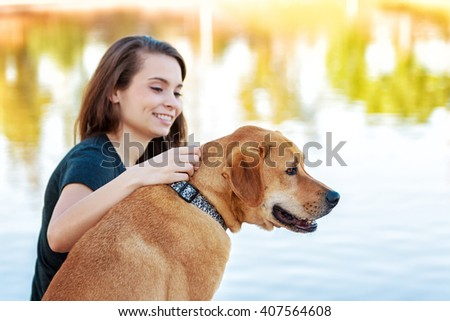 Happy girl and her Labrador crossbreed dog looking out over a lake. Selective focus on dog. - stock photo