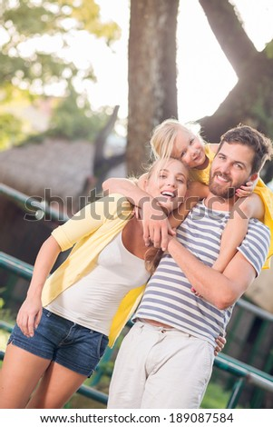Happy girl and her parents posing outdoors - stock photo
