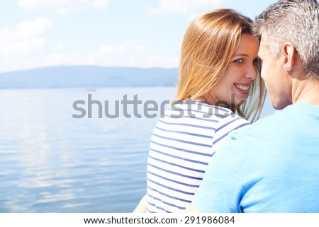 Happy girl and young man having romantic vacation by the sea - stock photo
