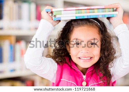 Happy girl at the library holding books - stock photo