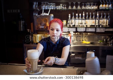 Happy girl Barista gives coffee  to the customers