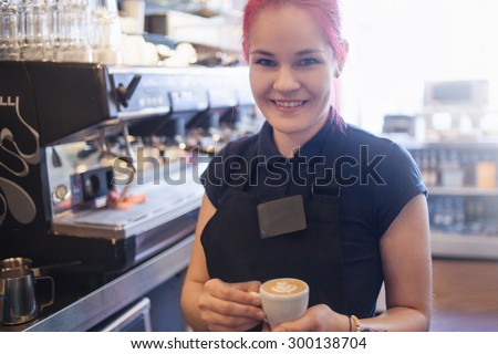 Happy girl Barista gives coffee  to the customers - stock photo