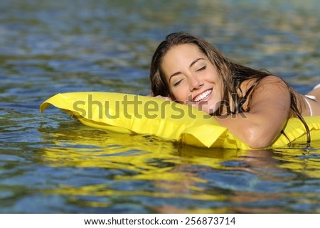 Happy girl bathing on the beach in summer vacation smiling with perfect teeth on a yellow mattress - stock photo
