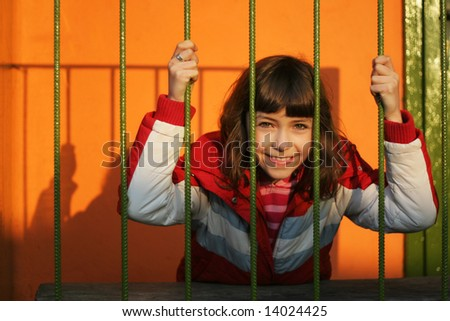 Happy girl behind bars