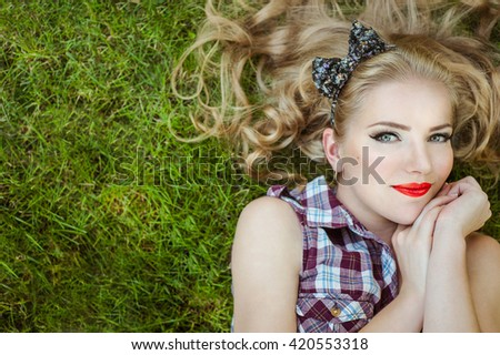 Happy Girl blonde smiling lying on the grass - stock photo
