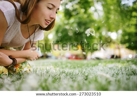 Happy girl blowing on dandelion field