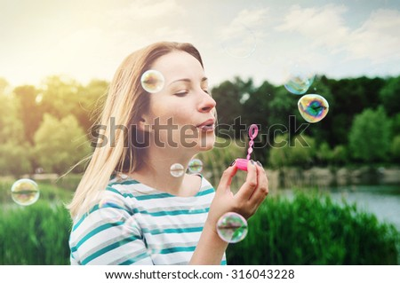happy girl blowing soap bubbles outdoors  - stock photo
