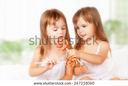 happy girl children twin sisters with lollipops candy - stock photo
