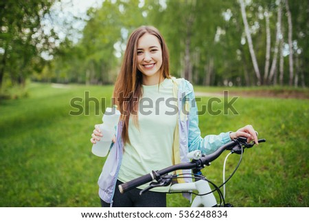 Happy girl cyclist standing with a mountain bike and drinking water. Adventure travel. Girl cyclist. Mountain bike. healthy lifestyle. Sort concept.