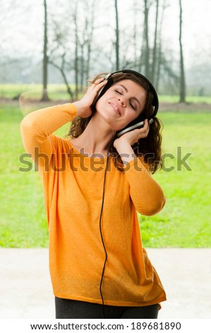 Happy girl dancing at home while listen music with headphones. She is in her house in front of the big window with view on nature - stock photo