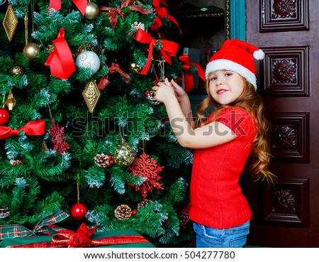 happy girl decorating a Christmas tree at home