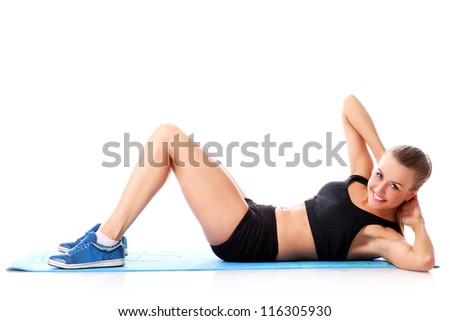 Happy girl doing fitness exercises on a mat over white background - stock photo
