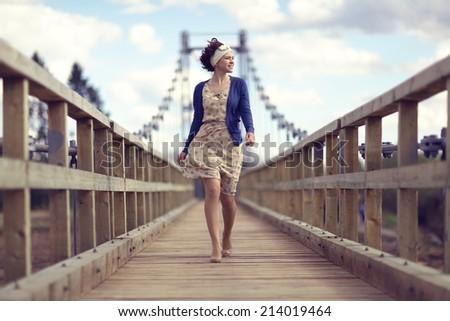 happy girl dress runs over the bridge - stock photo