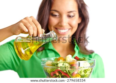Happy girl dressing fresh vegetable salad with olive oil - stock photo