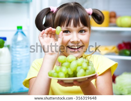 Happy girl eating grapes standing near refrigerator with fruits and vegetables - stock photo