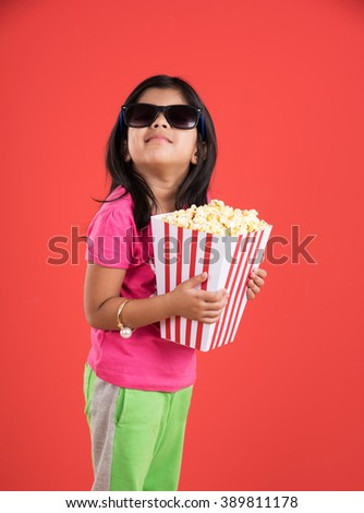 happy girl eating popcorn and wearing glasses, indian girl eating popcorn, asian girl and popcorn, small girl eating popcorn on red background