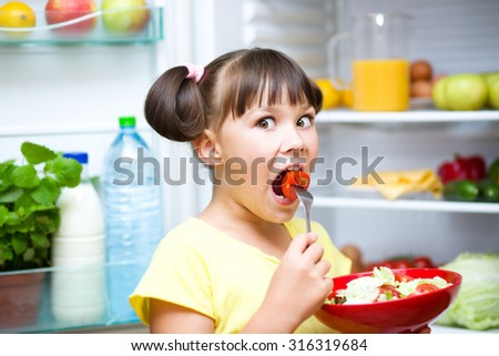Happy girl eating salad standing near refrigerator with fruits and vegetables - stock photo
