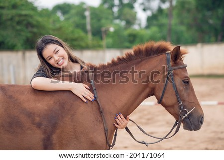 Happy girl embracing brown horse - stock photo