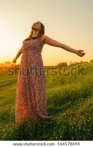 Happy girl enjoying beautiful summer sunset in the nature. - stock photo