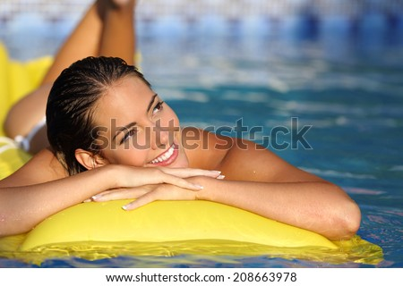 Happy girl enjoying summer vacations on a mattress in a pool and looking at side while thinking                 - stock photo