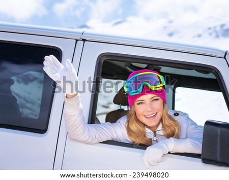 Happy girl enjoying winter sports, cheerful portrait of a woman sitting in the car and wearing ski mask, arrived to alpine ski resort, tourist travel on Christmas holidays - stock photo