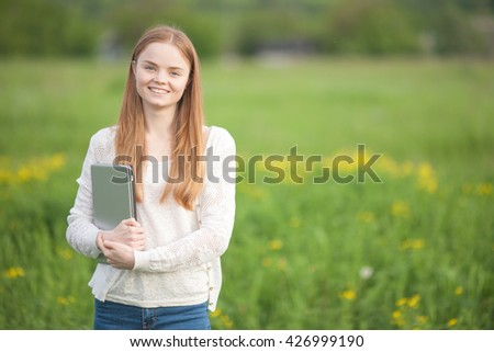 Happy Girl European appearance standing on the grass with a laptop on green nature background.