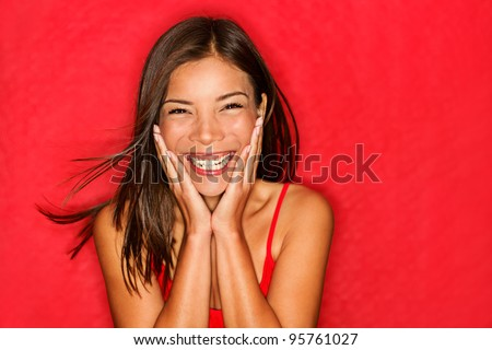Happy girl excited. Young woman smiling very happy surprised holding head being amazed on red background. Funky young multicultural Caucasian / Chinese Asian female model joyful on red background.