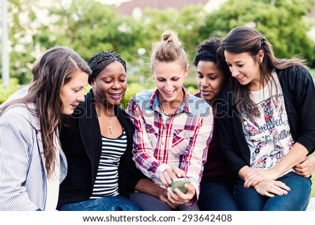 Happy girl friends looking at their smartphone and laughing