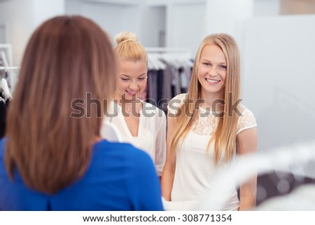 Happy Girl Friends Shopping for Clothes In a Clothing Store While One is Looking at the Camera. - stock photo