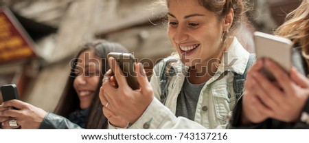 Happy girl friends watching internet social media in cell phone. Every one with his own phone