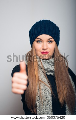 happy girl gesture all super, winter concept, studio photo isolated on a gray background