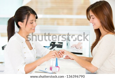 Happy girl getting her nails done at the beauty salon - stock photo