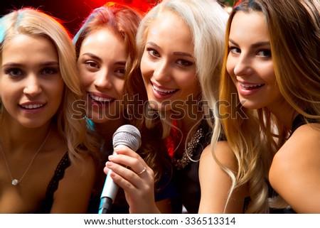 Happy girl having fun singing at a party - stock photo