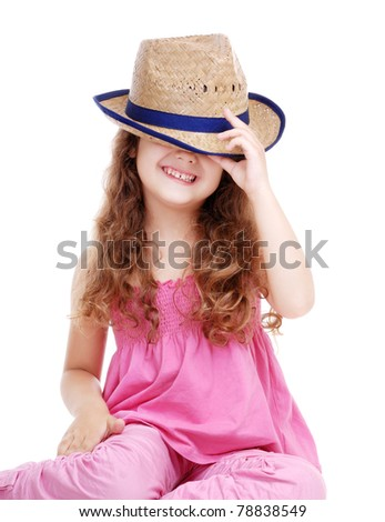 Happy girl hiding her face under the straw hat