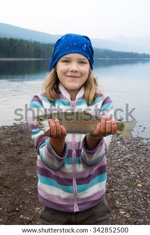 Happy girl holding a freshly caught trout in the hands of - stock photo
