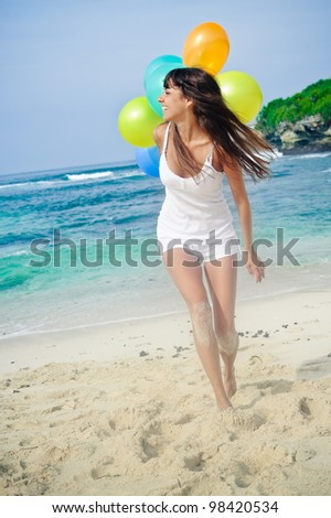 Happy girl holding bunch of colorful air balloons at the beach - stock photo