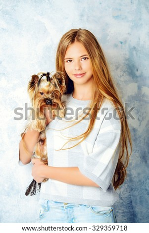 Happy girl holding her lovely yorkshire terrier dog.  - stock photo