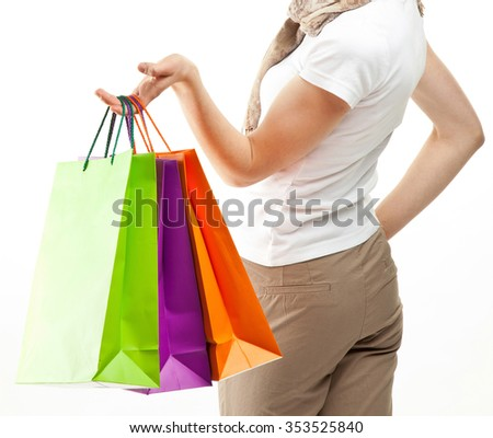 Happy girl holding multicolored shopping bags; white background