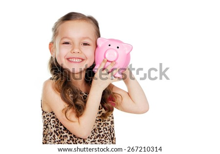 happy girl holding piggy bank at her ear closeup portrait - stock photo