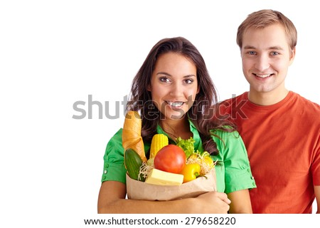 Happy girl holding sack with products and her boyfriend near by - stock photo