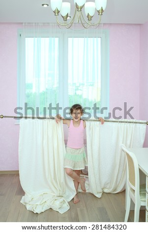 Happy girl holding the curtain with new drapes on the shoulders at the window in the room - stock photo