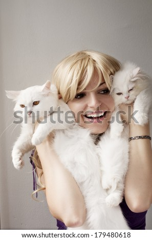 Happy girl holding two cats - stock photo