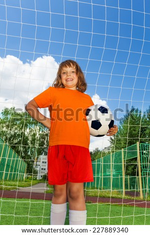 Happy girl holds football in one arm standing in front of white net of woodwork on sky and park background - stock photo
