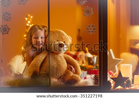 Happy Girl hugging Teddy Bear and watching through the window. Christmas greeting card. - stock photo