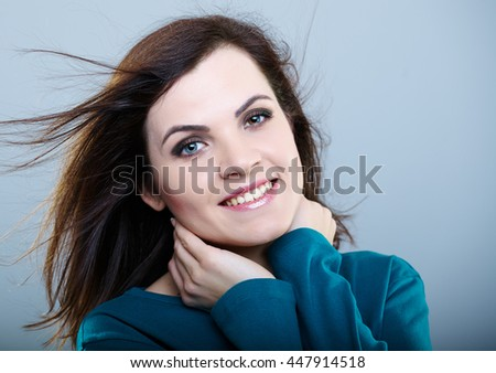 happy girl in a blue t-shirt with flying hair holds her neck hands on a gray background - stock photo