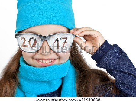 "Happy girl in a cap and scarf in funny glasses with the inscription ""2017"""