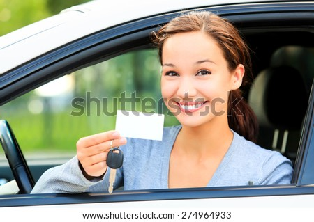 Happy girl in a car showing a key and an empty white card for your message.