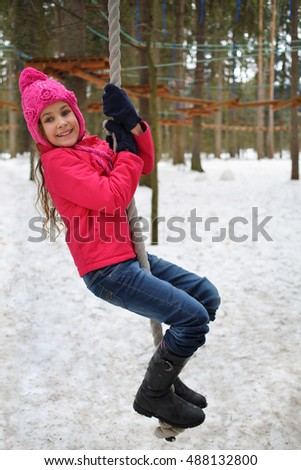 Happy girl in a pink jacket and hat hanging on rope in the winter