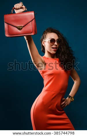 Happy girl in a red dress holding a red bag over his head, isolated on blue background. - stock photo